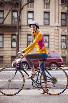 Portrait of female cyclist with bicycle on footpath - CAVF02879