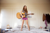 Smiling woman playing guitar on bed in bedroom - CAVF02891