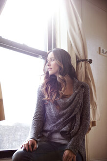 Low angle view of thoughtful young woman sitting on window - CAVF02894