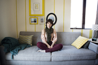 Portrait of smiling beautiful woman sitting on sofa at home - CAVF02957