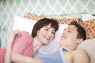Happy couple lying on bed at home - CAVF02960