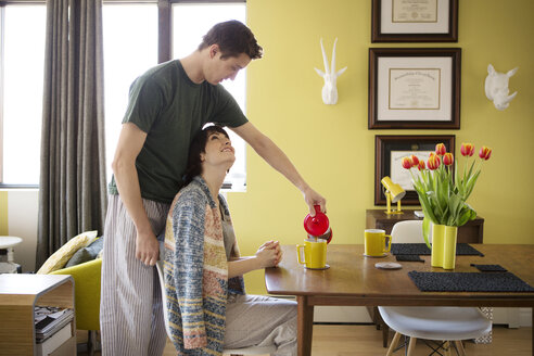 Woman looking at boyfriend serving coffee at table in home - CAVF02963