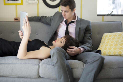 Woman looking at tablet computer while lying on man's lap on sofa - CAVF02975