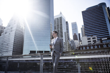 Businessman standing by railing against buildings in city on sunny day - CAVF03059