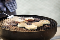 Cropped image of man preparing food on barbecue grill - CAVF03140