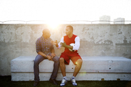 Soccer player talking with father while sitting on seat - CAVF03149