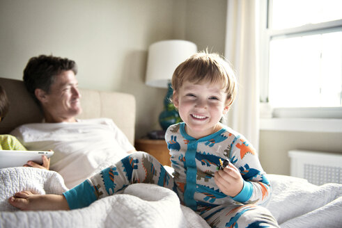 Happy boy enjoying with father while brother using tablet computer on bed at home - CAVF03227