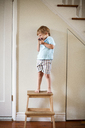 Happy boy standing on stool at home - CAVF03245