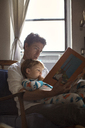 Father reading picture book for son while sitting on chair against window - CAVF03257