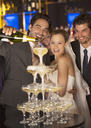 Groom pouring champagne pyramid at wedding reception - CAIF08150