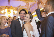 Friends throwing confetti over bride and groom at wedding reception - CAIF08153