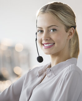 Businesswoman wearing headset in office - CAIF08168