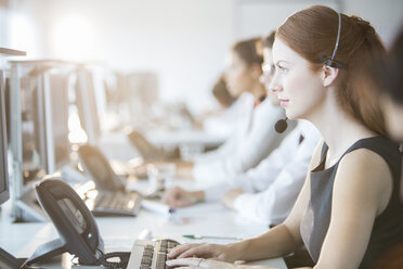 Businesswoman wearing headset in office - CAIF08177
