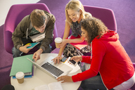 University students using laptop in lounge - CAIF08213