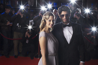 Serious celebrity couple on red carpet with paparazzi in background - CAIF08243