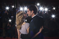 Paparazzi photographing celebrity couple kissing at red carpet event - CAIF08252