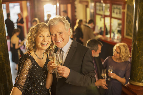 Portrait of well dressed couple toasting champagne flutes - CAIF08258