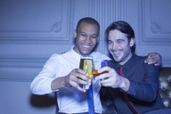 Well dressed men hugging and toasting beer and cocktail - CAIF08264
