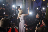 Celebrity couple waving to fans and paparazzi on red carpet - CAIF08267
