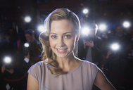 Close up portrait of smiling female celebrity with paparazzi in background - CAIF08282