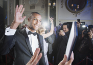 Well dressed male celebrity waving to fans and paparazzi at red carpet event - CAIF08285