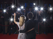 Rear view of celebrity couple waving to paparazzi at red carpet event - CAIF08300