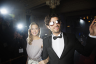 Well dressed celebrity couple waving to paparazzi on red carpet - CAIF08315