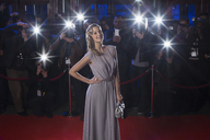 Portrait of well dressed female celebrity on red carpet with paparazzi in background - CAIF08324