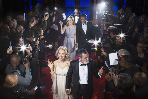 Well dressed celebrities waving to paparazzi on red carpet - CAIF08336