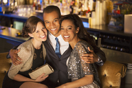Portrait of well dressed friends hugging in luxury bar - CAIF08339
