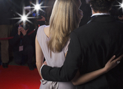 Close up rear view of celebrity couple hugging for paparazzi on red carpet - CAIF08348