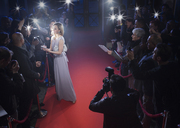 Well dressed female celebrity signing autographs and posing for paparazzi on red carpet - CAIF08351