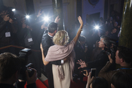 Rear view of well dressed celebrity couple waving to paparazzi on red carpet - CAIF08357