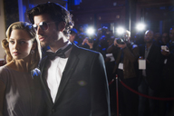 Close up of well dressed celebrity at red carpet event with paparazzi in background - CAIF08360