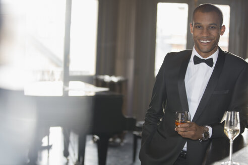 Portrait of well dressed man drinking cocktail in lounge - CAIF08393