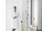Scientist smiling in food processing plant - CAIF08414