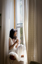 Thoughtful woman looking away while sitting on window sill at home - CAVF03315