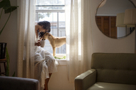 Woman with dog sitting on window sill at home - CAVF03318