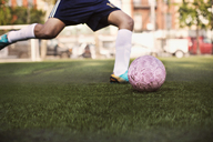 Low section of athlete kicking ball at soccer field - CAVF03366