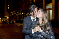Romantic man kissing girlfriend while standing on city street at night - CAVF03480