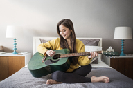 Woman playing guitar while sitting on bed at home - CAVF03579