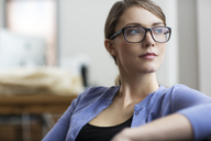 Confident woman looking away while sitting in office - CAVF03627