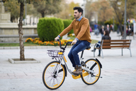 Young man riding rental bike in the city - JSMF00107