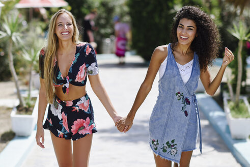Portrait of two happy young women holding hands in summer - JSMF00109