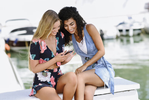 Two happy young women with cell phone at marina in summer - JSMF00112