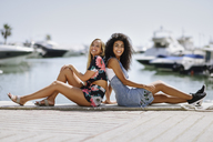 Two happy young women sitting on waterfront promenade in summer - JSMF00115