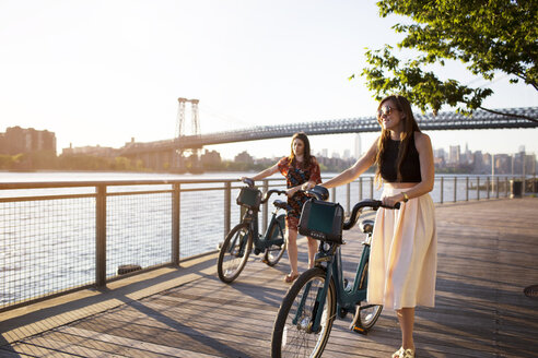Friends with bicycle walking on promenade against Williamsburg Bridge during sunset - CAVF03760