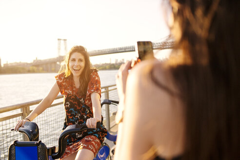 Woman photographing friend on bicycle against clear sky - CAVF03763