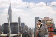 Businessman talking on mobile phone in office balcony - CAVF03802