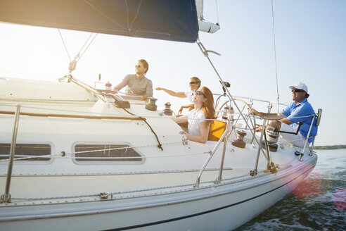 Happy friends sitting in yacht against clear sky - CAVF03928